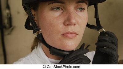 Caucasian woman putting on her helmet - Dressage jockey ...
