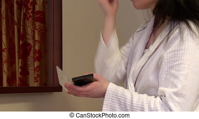 Caucasian woman putting skin powder at home
