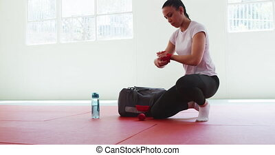 A mixed race teenage female judoka, kneeling on gym mats, wrapping her hands in preparation before judo training, her gym bag in the background, in slow motion.