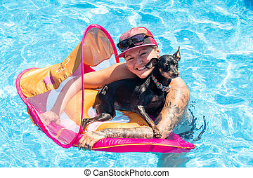 woman relaxing with black pinscher dog on a flotation device...