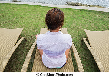 caucasian woman resting sitting in chair on the beach