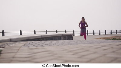 Front view of a young Caucasian woman wearing sports clothes and headphones running during a workout on a promenade, slow motion