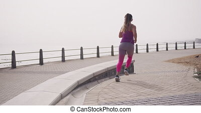 Rear view of a young Caucasian woman wearing sports clothes and headphones running during a workout on a promenade, slow motion