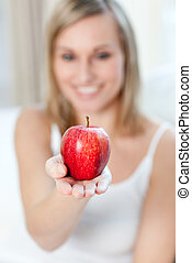 Caucasian woman showing an apple
