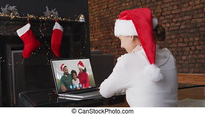 Caucasian woman spending time at home wearing santa hat, sitting by fireplace having video chat with friends on laptop screen, in slow motion.