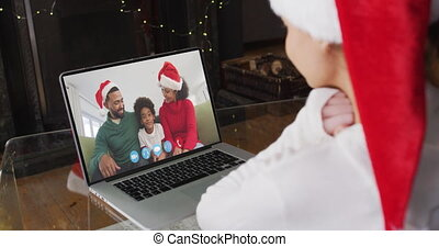 Caucasian woman spending time at home wearing santa hat, sitting by fireplace having video chat with friends on laptop screen, in slow motion.self isolation at christmas time during covid 19 pandemic