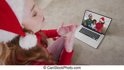 Caucasian woman spending time at home wearing santa hat, sitting on floor having video chat with friends and family on laptop screen, blowing kisses in slow motion.