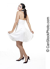 caucasian woman standing in white dress and heels