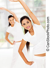 caucasian woman stretches her body for fitness with friend on background