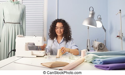 Caucasian woman tailor reeling thread at workplace. bobbins...