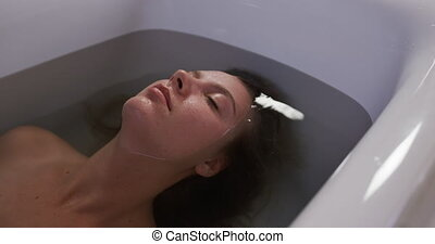 Caucasian woman taking bath in hotel - Side view of a ...