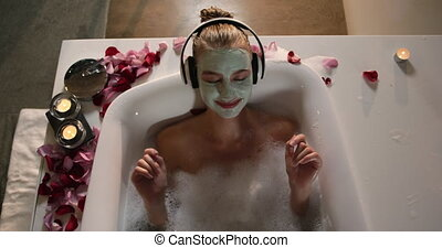 Caucasian woman taking bath while listening music in hotel...