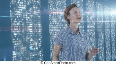 Caucasian woman touching a screen over server room in background