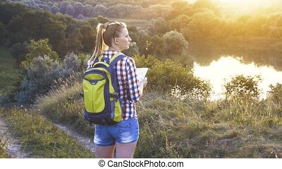 caucasian woman tourist with a map and a backpack on a hike navigates the terrain. Leisure activity
