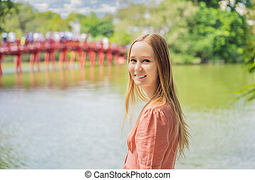 Caucasian woman traveler on background of Red Bridge in public park garden with trees and reflection in the middle of Hoan Kiem Lake in Downtown Hanoi. Vietnam reopens after coronavirus quarantine COVID 19