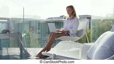 Caucasian woman using laptop on balcony - Side view of a ...
