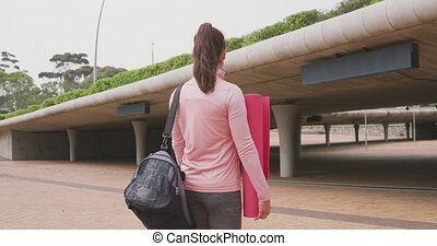 Caucasian woman walking under bridge with yoga mat - Rear ...