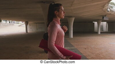 Caucasian woman walking under bridge with yoga mat - Side ...