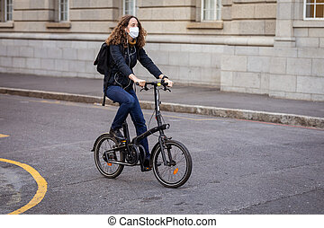 Caucasian woman out and about in the city streets during the day, wearing a face mask against air pollution and covid19 coronavirus, cycling