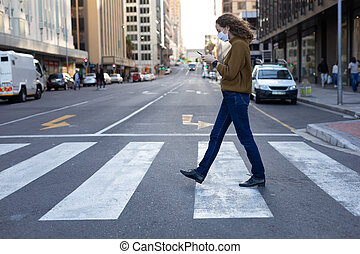 Caucasian woman out and about in the city streets during the day, wearing a face mask against covid19 coronavirus, walking on a pedestrian crossing and using smartphone