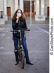 Caucasian woman wearing a protective mask on her bike, ...