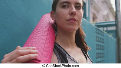Caucasian woman with a yoga mat - Side view of a Caucasian ...
