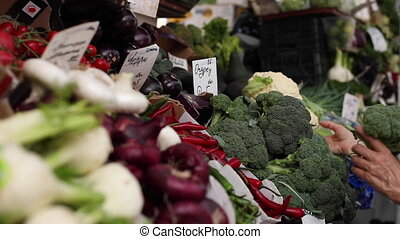 Caucasian woman with blond hair in medical protective mask chooses broccoli and cauliflower at market.