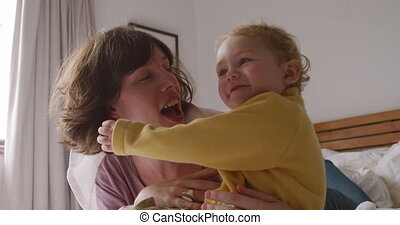 Caucasian woman with her baby at home in bedroom - Side view...