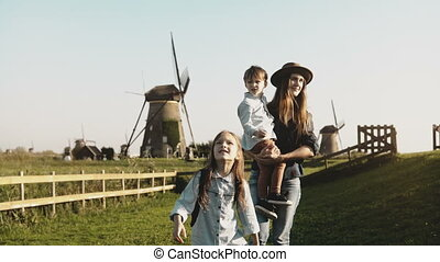 Caucasian woman with two kids near a windmill farm. Mother,...