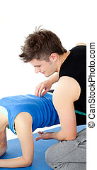 Caucasian woman working out assited by her personal trainer