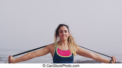 Front view close up of a young Caucasian woman wearing sports clothes using an exercise band during a workout on a promenade, slow motion