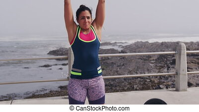 Caucasian woman working out on the docks - Front view of a ...