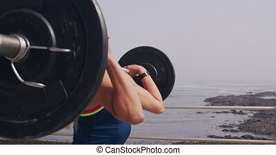 Side view close up of a young Caucasian woman wearing sports clothes lifting weights during a workout on a promenade, slow motion