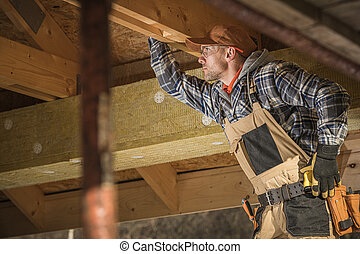 Caucasian Worker Checks Wooden Framing Of New Attic.