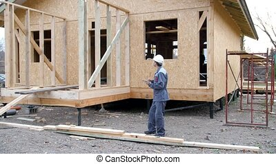 Caucasian worker in front of a house. Architect or builder check plans in a half built timber frame house. Builder on a construction site with a tablet. 4k