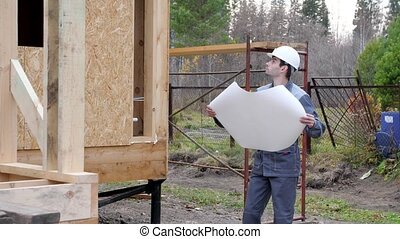 Caucasian worker in front of a house. Architects or builder check plans in a half built timber frame house. Builder on a construction site with a plan. 4k