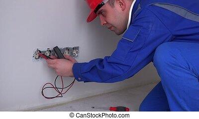 Caucasian worker testing wall socket. Static closeup shot....