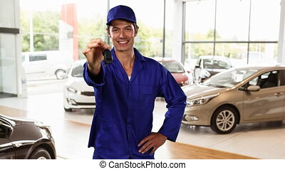Caucasian worker wearing a blue overwall and hat in a car ...