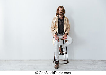 Caucasian young bearded man sitting isolated over grey wall