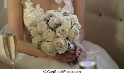 Caucasian young bride in wedding dress sitting on sofa with bouquet