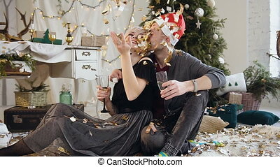 Caucasian young couple are celebrating Christmas or New Year together, they sitting on the floor, drinking wine near of christmas decorations and christmas tree at home