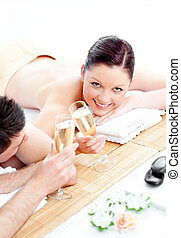 Caucasian young couple lying on a massage table and drinking champagne in a spa center