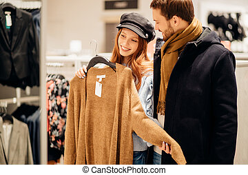 caucasian young couple want to buy new outfit for wife