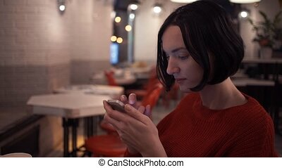 Caucasian young girl using smartphone sitting in cafe in...