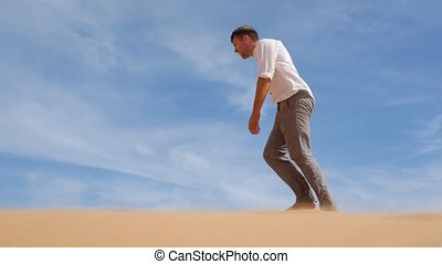 Caucasian young man going straight on his way on sandy...