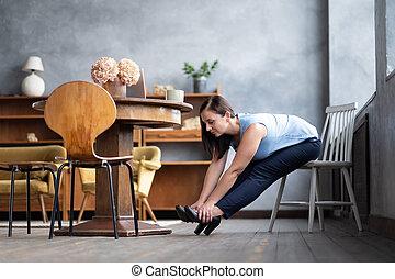 Caucasian young woman doing paschimottanasana sitting on chair.