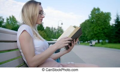 Caucasian young woman hipster reading a book on the bench outdoors