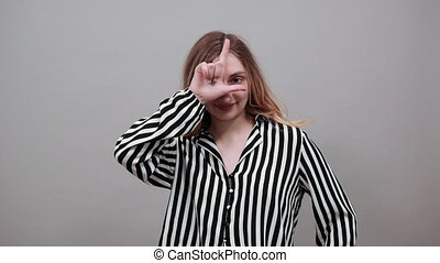 Caucasian young woman looking at camera, doing loser gesture...