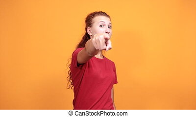 Caucasian young woman in red shirt isolated on orange background in studio pointing directly, looking happy. People sincere emotions, health concept.