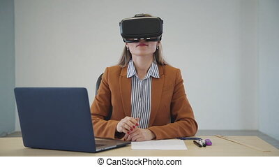 Caucasian young woman wearing virtual reality glasses scrolling in the air in the office.
